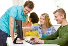 Smiling students in computer class at school. Education, technology and school concept - smiling students in computer class at school Stock Photography