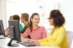 Smiling students in computer class at school. Education, technology and school concept - smiling female students in computer class at school having discussion Royalty Free Stock Image