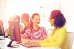 Smiling students in computer class at school. Education, technology and school concept - smiling female students in computer class at school having discussion Royalty Free Stock Photography