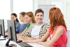 Smiling students in computer class at school. Education, technology and school concept - smiling students in computer class at school having discussion Royalty Free Stock Photography