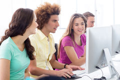 Smiling students in computer class Stock Photos