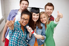 Smiling students with diploma showing thumbs up Royalty Free Stock Photos