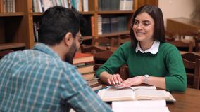 Students Give High Five. Smiling students discussing material while working on project, attractive bearded boy and long-haired brunette sitting at brown library stock footage