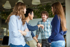 Smiling students enjoyng conversation in classroom Royalty Free Stock Photography