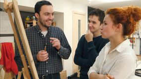 Smiling students and female art teacher analyzing artwork on easel. Professional shot on Lumix GH4 in 4K resolution. You can use it e.g. in your commercial royalty free stock photo