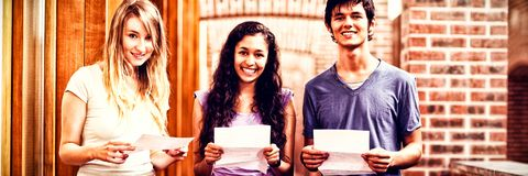 Smiling students holding paper. In corridor Stock Photography