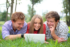 Smiling students with laptop Stock Photography