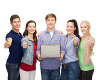 Smiling students with laptop computer. Education, advertisement and new technology concept - smiling students with laptop computer blank screen showing thumbs up Royalty Free Stock Photography