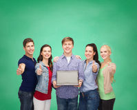 Smiling students with laptop computer Royalty Free Stock Images