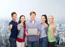 Smiling students with laptop computer Stock Images