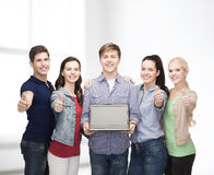 Smiling students with laptop computer. Education, advertisement and new technology concept - smiling students with laptop computer blank screen showing thumbs up Stock Photography