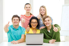 Smiling students with laptop at school. Education and college concept - five smiling students with laptop at school showing thumbs up Royalty Free Stock Images