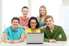 Smiling students with laptop at school. Education, technology and college concept - five smiling students looking at laptop at school Royalty Free Stock Photography