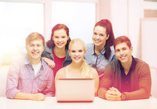 Smiling students with laptop at school stock image