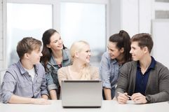 Smiling students with laptop at school Stock Photo