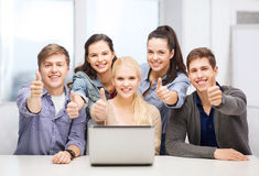 Smiling students with laptop showing thumbs up. Education, technology and internet concept - smiling students with laptop showing thumbs up at school Royalty Free Stock Image