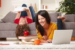 Smiling students learning at home. Happy students studying at home in living room with books and laptop, looking at camera smiling royalty free stock images