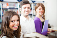 Smiling students in a library. Portrait of three smiling students in a library Royalty Free Stock Images