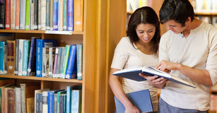Smiling students looking at a book Royalty Free Stock Image