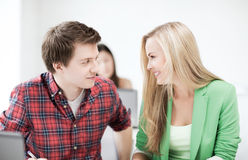 Smiling students looking at each other at school Royalty Free Stock Images