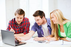 Smiling students looking at laptop at school Royalty Free Stock Photography