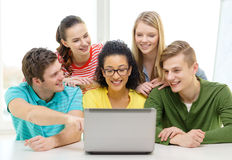 Smiling students looking at laptop at school Stock Photos
