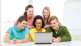 Smiling students looking at laptop at school Stock Images