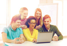 Smiling students looking at laptop at school Stock Image