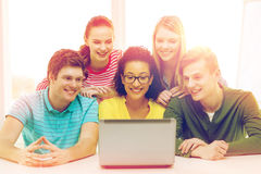 Smiling students looking at laptop at school Royalty Free Stock Image