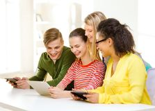 Smiling students looking at tablet pc at school Royalty Free Stock Images