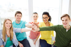 Smiling students making high five gesture sitting Stock Photography