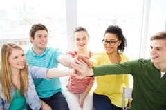 Smiling students making high five gesture sitting Royalty Free Stock Images