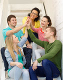 Smiling students making high five gesture sitting stock images