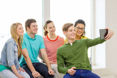 Smiling students making picture with tablet pc Royalty Free Stock Images