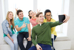 Smiling students making picture with tablet pc Stock Photo