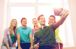 Smiling students making picture with tablet pc Royalty Free Stock Image
