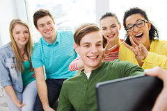 Smiling students making selfie with tablet pc Royalty Free Stock Photo