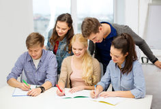 Smiling students with notebooks at school Stock Image