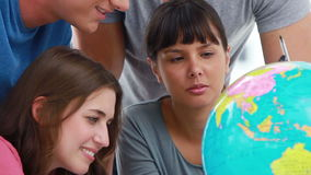 Smiling students pointing at countries on a globe stock footage