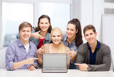 Smiling students pointing to blank lapotop screen Stock Image