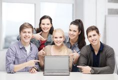 Smiling students pointing to blank lapotop screen Royalty Free Stock Photo