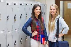 Smiling students posing near locker Royalty Free Stock Photos