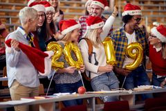 Smiling Students in Santa hat holding 2019 golden balloons at New Year party royalty free stock image