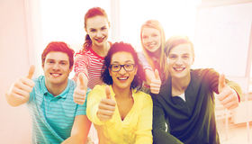 Smiling students at school showing thumbs up Stock Images