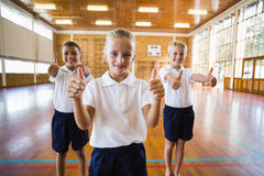Smiling students showing thumbs up in school gym. Portrait of students showing thumbs up in school gym Stock Images