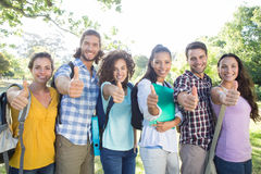 Smiling students showing thumbs up. On a sunny day Royalty Free Stock Photo