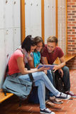 Smiling students sitting on bench using tablet Royalty Free Stock Images
