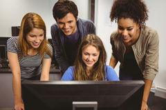 Smiling students sitting at desk using computer together Stock Photo