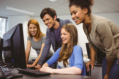 Smiling students sitting at desk using computer together Royalty Free Stock Photo