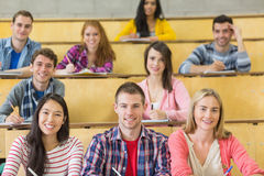 Smiling students sitting at the lecture hall. Portrait of  smiling students sitting at the lecture hall while writing Stock Photography